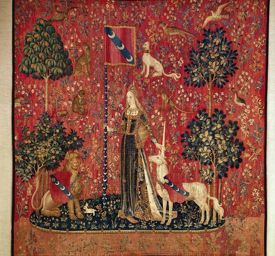 The Lady and the Unicorn 2/6 - Touch The lady stands with one hand touching the unicorn's horn, and the other holding up the pennant. The lion sits to the side and looks on.