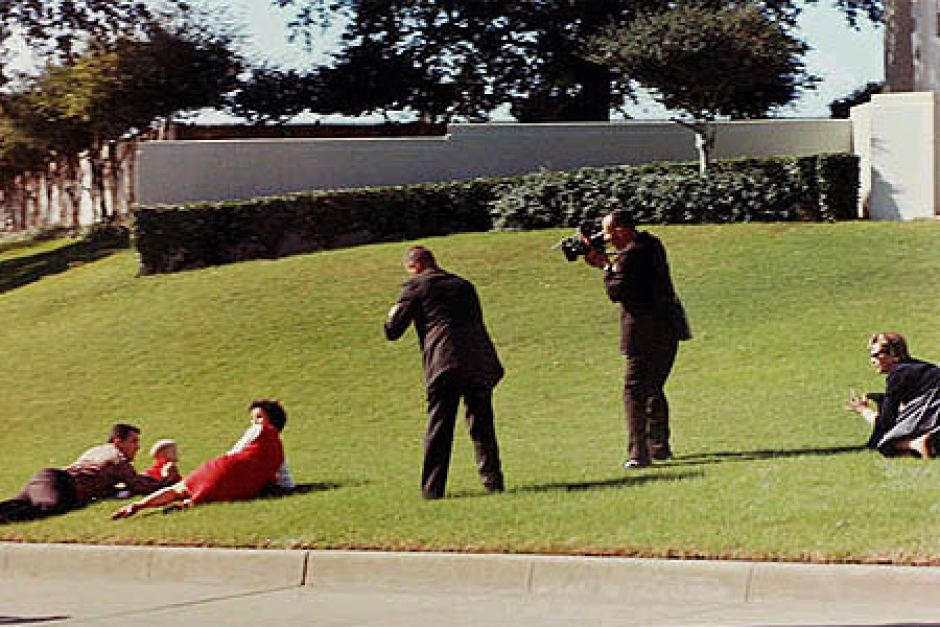 People dive for cover on the grassy knoll. - ABC News (Australian Broadcasting Corporation)