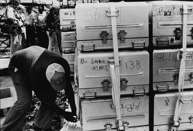An unidentified man a strap onto a stack of aluminum coffins for shipment to the United States, following the more than 900 deaths in the mass suicide staged in Jonestown by members of the People's Temple and their leader, the Reverend Jim Jones, Georgetown, Guyana, Nov. 23, 1978. A group of photographers and police officers stand in the background.